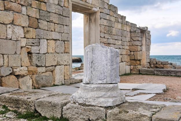 해변에 있는 고대 그리스 사원 유적 중 대리석 기둥 조각