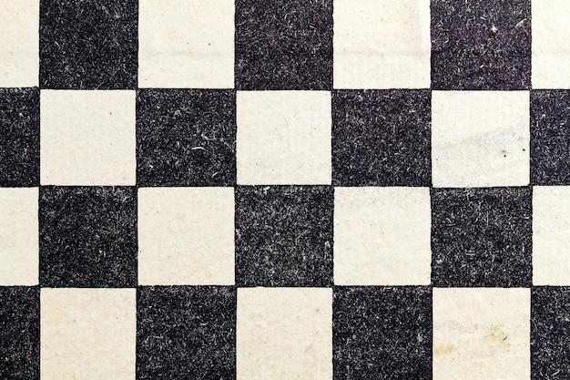 Фрагмент бумажной шахматной доски. абстрактный черный и белый фон