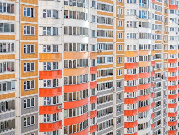 다층 아파트 건물의 창문이있는 벽 조각.