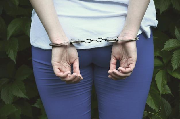 手錠で手を持つ若い刑事少女の体の断片