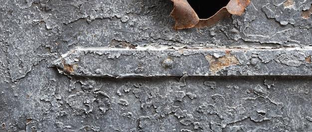 때때로 금이 간 페인트가 있는 오래된 금속 표면의 조각