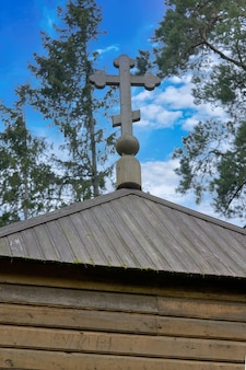 Фрагмент старой деревянной христианской церкви с крестом на фоне неба
