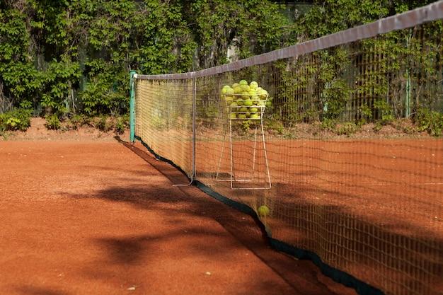 야외 클레이 테니스 코트의 조각 바구니에 있는 테니스 공은 그물 선택적 초점 근처에 있습니다