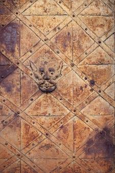 문 두 들기는 사람과 고대의 녹슨 금속 문 조각.