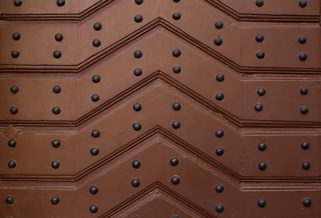 釘付きストラップで作られた茶色の木製ドアの断片。クローズアップ写真