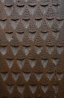 刻まれた茶色のドアの断片。クローズアップ写真