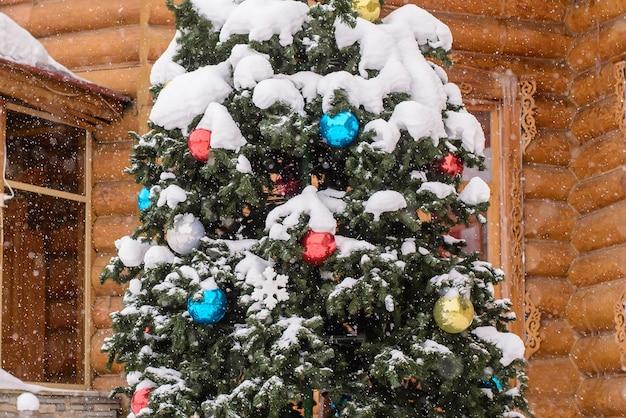 Фрагмент елки с разноцветными шарами на ветках на улице на фоне деревянного дома