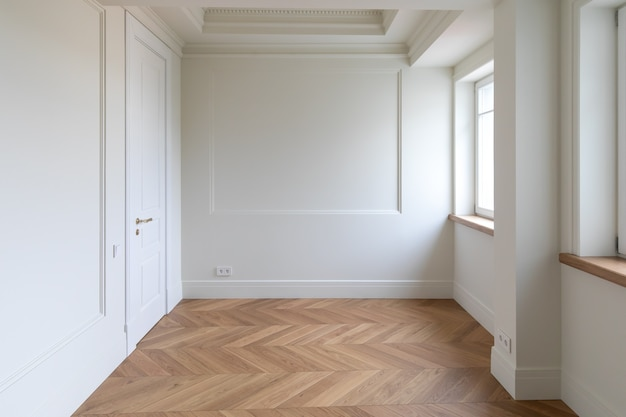 헤링본 쪽모이 세공 마루 바닥과 몰딩 및 스커트 보드가 설치된 벽면 패널이있는 고전적인 인테리어 조각. copyspace와 흰 벽입니다.