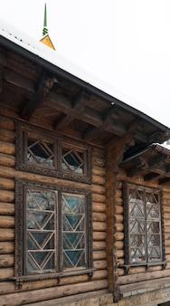 Фрагмент загородного деревянного дома со снегом на крыше и резьбой по окну.