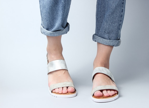 ブルージーンズと白のトレンディなレザーサンダルで女性の足のフラグメント。女性のスタイリッシュな夏の靴。