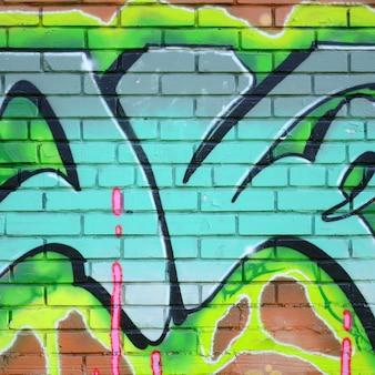 낙서 도면의 조각. 오래된 벽은 거리 예술 문화 스타일의 페인트 얼룩으로 장식되어 있습니다. 녹색 색조의 컬러 배경 텍스처