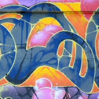 낙서 도면의 조각. 오래된 벽은 거리 예술 문화 스타일의 페인트 얼룩으로 장식되어 있습니다. 따뜻한 색조의 컬러 배경 텍스처