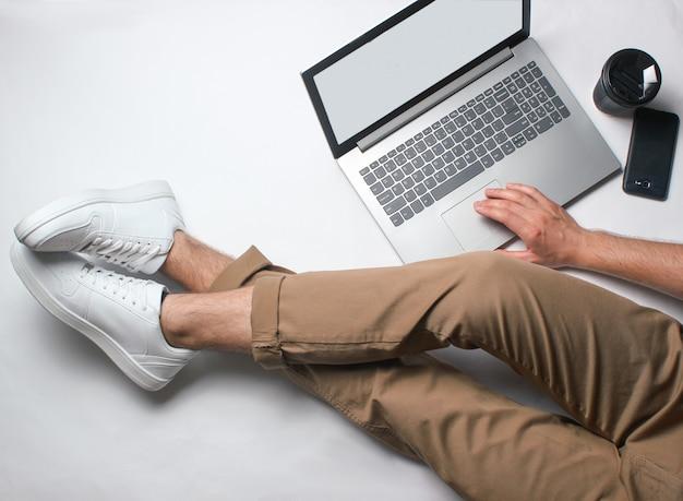 Фрагмент мужских ног в бежевых брюках и белых кроссовках, сидя на белом. человек, используя современный ноутбук. интернет работник, фриланс, работа на дому, человек работает. вид сверху