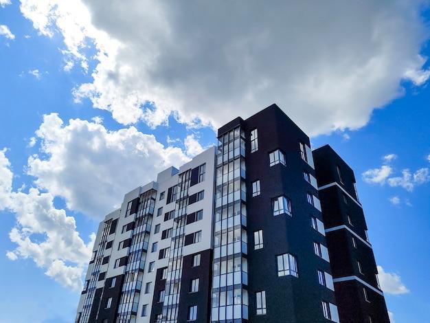 푸른 흐린 하늘 맞은편에 있는 현대적인 아파트 건물의 조각