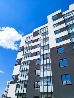 푸른 하늘 맞은편에 있는 현대적인 아파트 건물의 조각