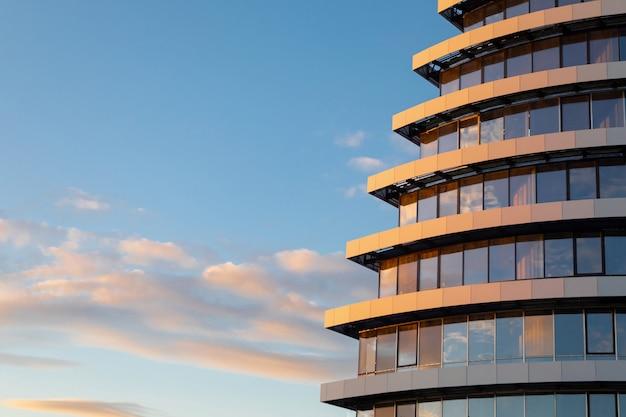 Фрагмент современного стеклянного фасада строящегося здания на фоне неба