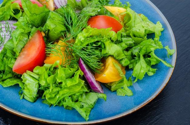 野菜とレタスのクローズアップ、トップビューでプレートのフラグメント。スタジオ写真