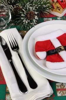 Фрагмент новогоднего стола сервировочного пальто деда мороза со столовыми приборами