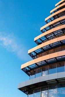 Фрагмент недостроенного многоэтажного жилого дома или коммерческой недвижимости на фоне голубого неба