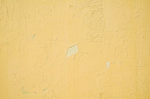 Фрагмент желтой стены с царапинами и трещинами. шероховатая потрескавшаяся желтая краска для стен отслаивается. старая краска отслаивается от фона текстуры стены.