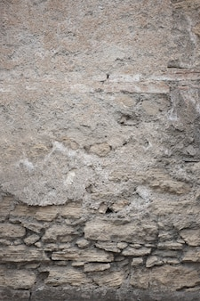 Fragment of old grungy texture with chipped paint and cracks or grey concrete wall and cement surface