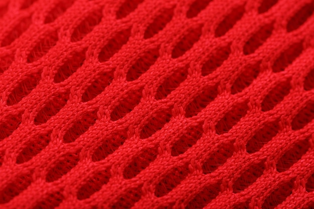 Fragment of a perforated toe of a red sneaker in full-screen close-up. texture of the texture of the material of sports shoes.
