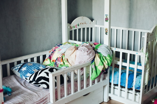Fragment of a photo of a children's room with scattered things, pillows and coverlets on the beds