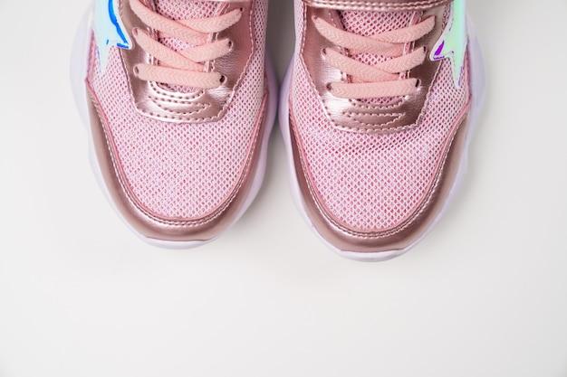 프래그먼트 핑크 샤이니 스니커즈. 여아를 위한 세련되고 세련된 밝은 신발. 신발 가게.