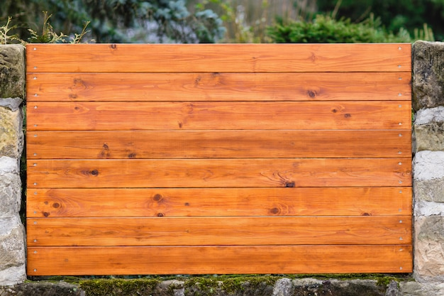 Fragment of wooden fence with horizontal planks and columns of natural stone