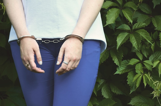 Fragment of a young criminal girl's body with hands in handcuffs