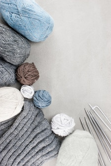 Fragments of knitted clothes and coils of wool on the textured concrete background