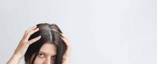 若い女性の頭の白髪の断片初期の白髪の概念