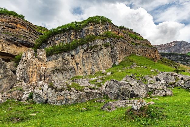 Фрагменты скал на зеленом лугу в высокогорье