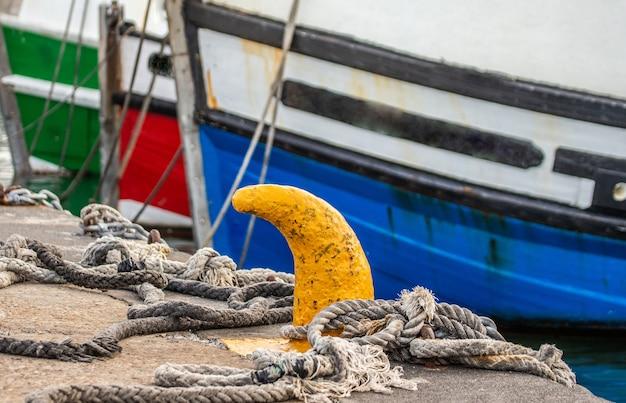 桟橋にロープで結ばれた漁船の船首の断片。