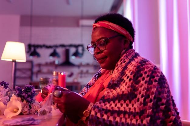 Аромат. пухлая афроамериканка-гадалка в золотых часах с довольным видом держит сумку с ароматами
