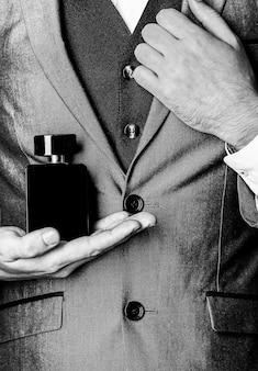 香りのにおい。男性の香水。ファッションケルンボトル。香水のボトルを持っている男。男性はスーツの背景に手で香水。黒と白。