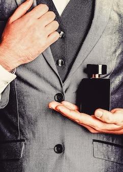 향수 냄새. 남자 향수. 패션 향수 병. 향수 병을 들고 남자입니다. 양복 배경에 손에 남자 향수입니다.