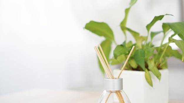 香りは、白い背景の上に花瓶に花とガラス瓶に固執します。芳香剤スティック。セレクティブフォーカス