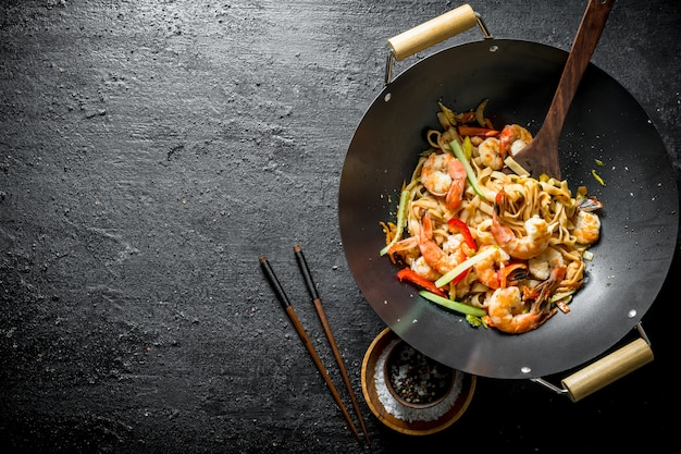 Fragrant asian udon noodles in a wok pan. on black rustic