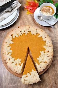 크림과 계피를 곁들인 호박 커피 한 잔과 함께 탁자 위에 있는 향기로운 가을 호박 파이