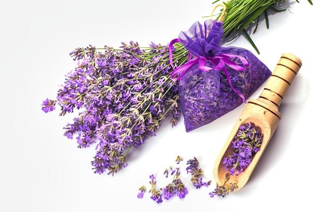 흰색 표면에 라벤더 꽃과 향기로운 가방 또는 파우치. 라벤더 향 주머니 근처 라벤더의 sprigs.