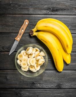 香りのよいバナナとバナナのスライスをナイフでガラスのボウルに入れます。黒い木製の背景に。