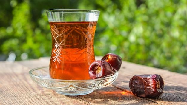 Fragrant black tea on wooden table in garden