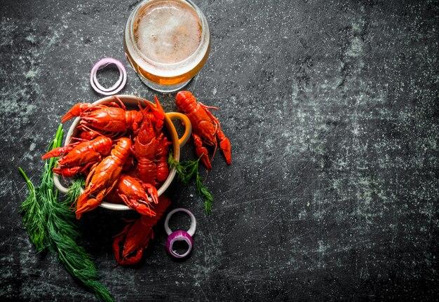 맥주, 딜 및 양파 링과 함께 그릇에 향기로운 삶은 가재. 어두운 소박한 배경에