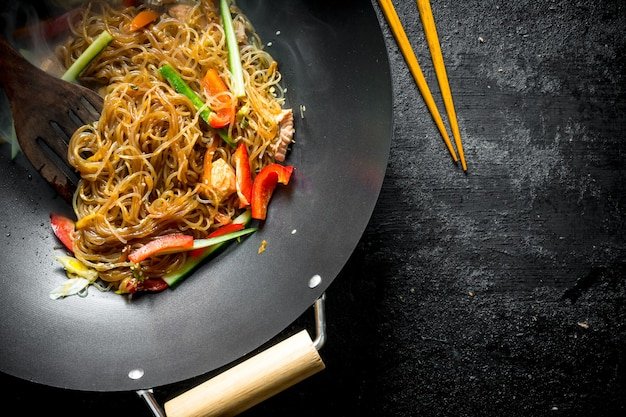 Fragrant chinese cellophane noodles in a frying pan wok with salmonnd vegetables on dark wooden table