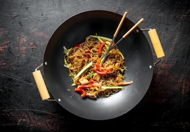 暗い素朴なテーブルの上にサーモンド野菜とフライパン中華鍋で香りのよい春雨