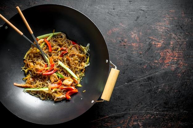 어두운 소박한 테이블에 연어 야채와 함께 프라이팬 냄비에 향기로운 중국 셀로판 국수