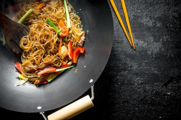 어두운 나무 테이블에 연어 야채와 함께 프라이팬 냄비에 향기로운 중국 셀로판 국수