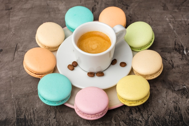 香り高いコーヒーとカラフルなマカロンクッキーが皿の上の円形に配置されています