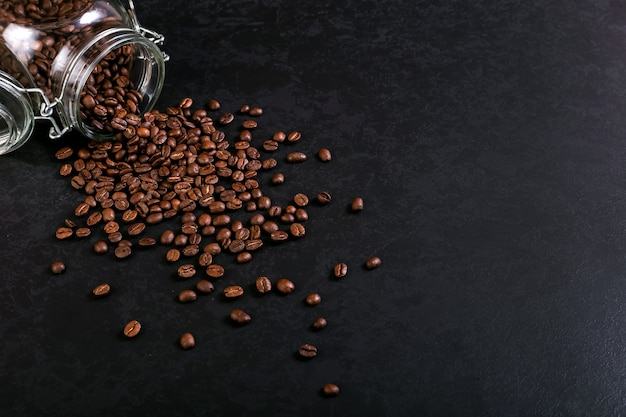 Fragrant coffee beans are scattered from a jar on a rustic tabletop background